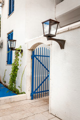 blue gates in white wall with gas lamp at greek style