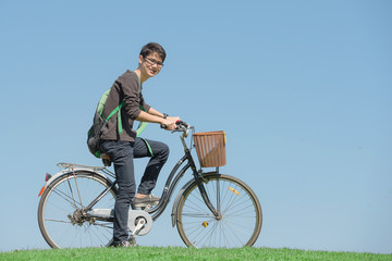 Happy student rides a bicycle in park