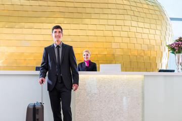 Mann auf Geschäftsreise bei Anreise im Hotel