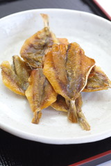 Small sweet dried fish snack on white plate
