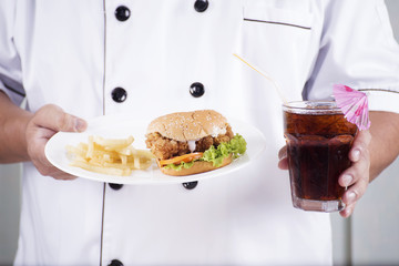 chef present a burger and cola drink