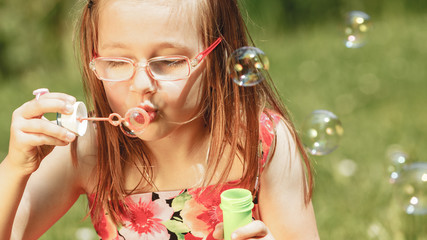 Little girl having fun blowing soap bubbles in park.