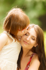Little girl hugging his mother expressing tender feelings. Love.