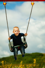 Little boy having fun at the playground on swing