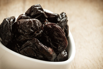 dried plums prunes in white bowl on wooden table