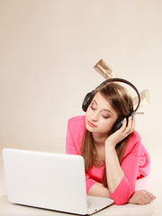 Girl with headphones and laptop listening to music