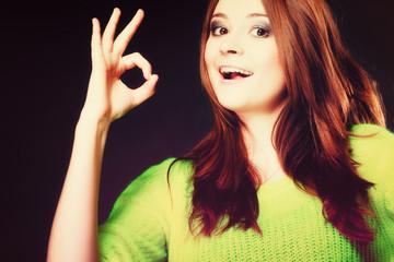 teen girl showing ok sign hand gesture on black
