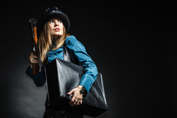 beautiful steampunk woman with bag and gun on black.