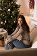 Woman drinking tea near Christmas tree