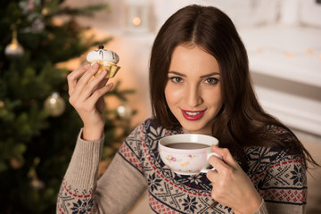 Woman drinking tea near Christmas tree