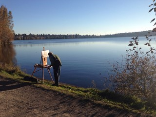 man paiting by a lake