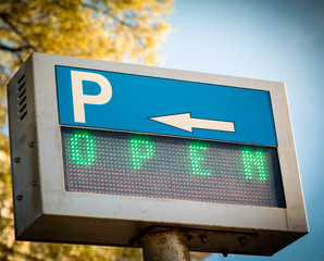 Open... parking  sign in front a parking lot