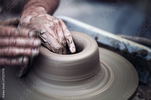Hands working on pottery wheel ,  artistic  toned - 73271719