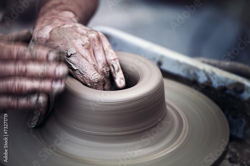 Leinwandbild Motiv Hands working on pottery wheel ,  artistic  toned