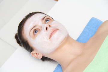 Beautiful young blue eye woman with clay facial mask