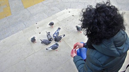 Girl feeding flock of pigeons on town square in London