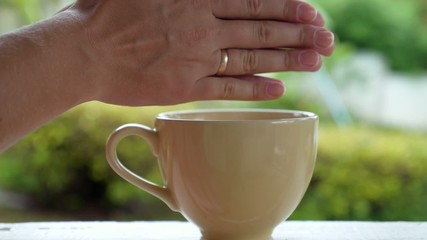 Woman Holding Steaming Hot Cup of Tea and Warming Hands.