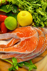 Portion of fresh salmon fillet with lemon, lime and parsley