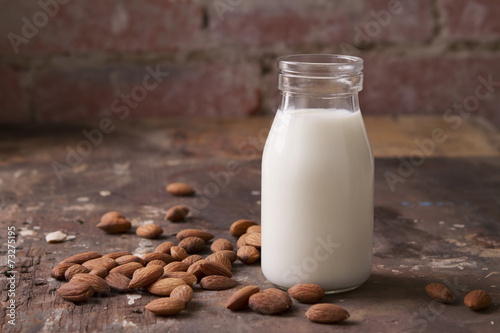 Almond milk in a glass jar with almonds - 73275195
