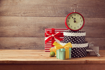 Gift boxes and watch on wooden table. New Year celebration