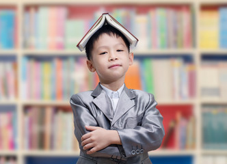 Asian boy with book on his head in school library