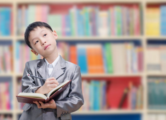 Asian boy reading book in school library