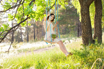 Young woman is swinging on a swing in summer forest.