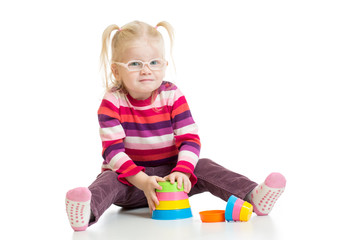 Funny child in eyeglases playing colorful pyramid toy isolated