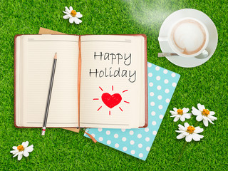 Happy Holiday on notebook with coffee cup on grass field.