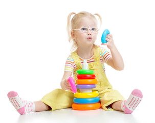 Funny kid in eyeglases playing colorful pyramid toy isolated