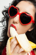 Hot brunette woman with red glasses sexy eating banana