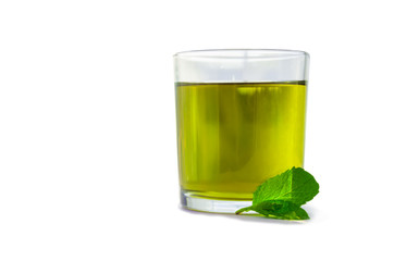 Mint tea in a glass with mint leaves next to it on white