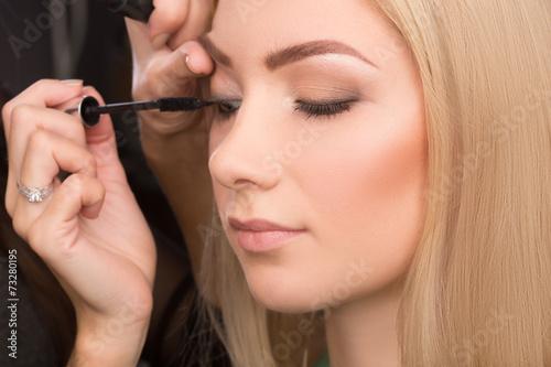 makeup artist puts mascara on the eyelashes. - 73280195