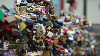 Love locks on a bridge, lovers padlocks hanging enormous amount