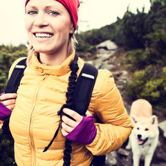 Happy woman hiking vintage mountains with dog