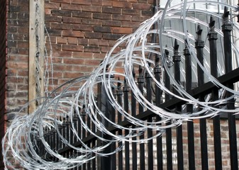 Iron fence with razor and barbed wire