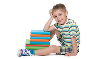 Little blond boy near the pile of books