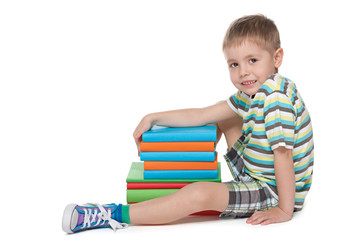 Cute blond boy with books