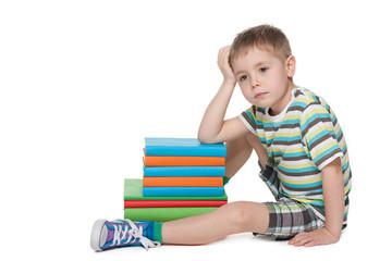 Sad little boy near books