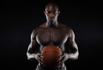 Muscular young man shirtless holding a basketball