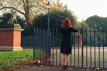 Woman leaning on gate in park