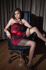 Sexy woman with red wear on the chair