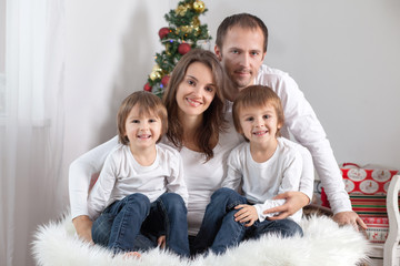 Portrait of friendly family looking at camera on Christmas eveni