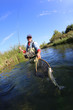 Fly fisherman catching rainbow fish - 73284516