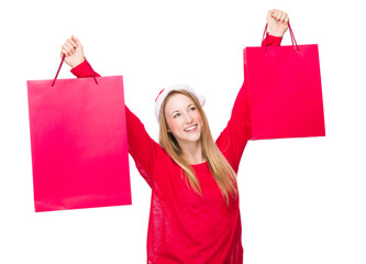 Excited woman with xmas hat and raise shopping bag up
