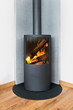 Modern burning stove in a corner of room - 73285184
