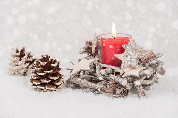 Burning candle and pine cone in the snow