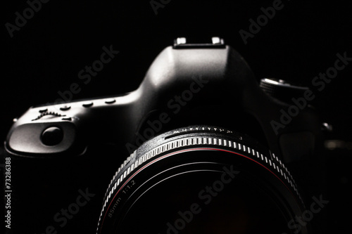 Professional modern DSLR camera low key image - 73286388
