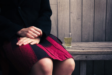 Woman sitting on bench with glass of beer