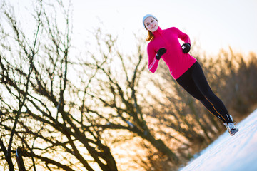 Winter running - Young woman running  on a cold winter day